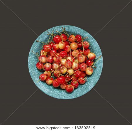 Cherry fruit. Sweet cherries in blue ceramic bowl. Top view. Ripe and tasty cherries on a wooden background.