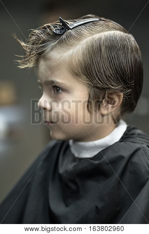 Child in the black salon cape on the blurry background in the barbershop. He has a hairpin on the head. Closeup vertical photo.