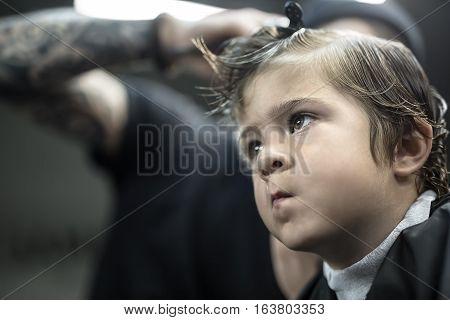Wide aperture closeup portrait of the kid who is in the barbershop. He wears a black salon cape. Horizontal.