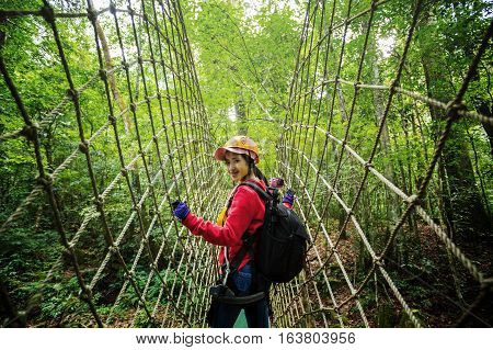 Asian woman traveler with a backpack walking on the bridge jungle lifestyle concept are walking on a rope over the tree and turned to smile for the camera.