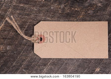 Rustic blank gift tag on old wooden board