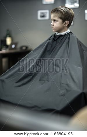 Dreaming little boy in a black salon cape in the barbershop. He looks to the side. Wide aperture closeup photo. Vertical.