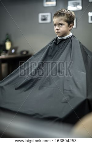 Inscrutable little boy in a black salon cape in the barbershop. He looks in front of himself. Vertical.