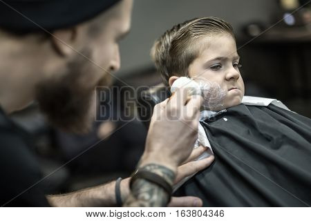 Positive kid in a black salon cape in the barbershop. Bearded barber with a tattoo applies shaving foam with the help of the shaving brush on the boy's face. Closeup low aperture photo. Horizontal.