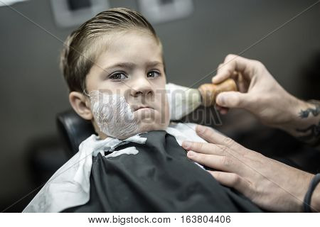 Funny kid in a black salon cape in the barbershop. Barber with a tattoo applies shaving foam with the help of the shaving brush on his face. Closeup low aperture photo. Horizontal.