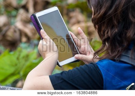 Woman sitting near the pond handle Tablet.