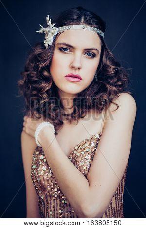 Fashion photo of beautiful girl wearing sparkling evening dress. Professional make-up and hairstyle. Perfect skin. Fashion photo. Gatsby style.