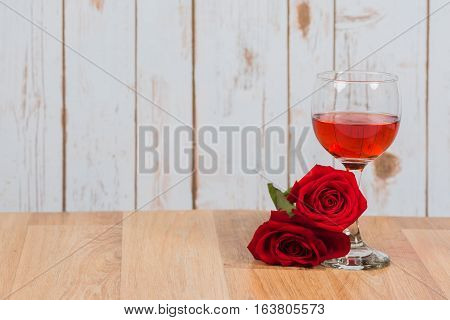 Glass of wine with two roses on wood table