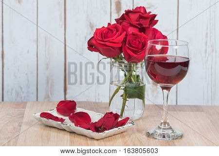 Wine and roses with petals laying on a vintage dish