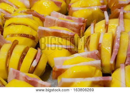 Preparing to bake in the oven at protven potatoes with bacon. Top sprinkled with salt and black pepper. Potatoes with cuts. The slit inserted pieces of meat.