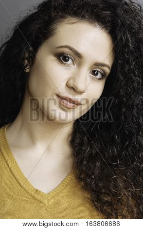Be serious. Brown-eyed woman with curly locks looking straight at camera keeping smile on the face posing over grey background