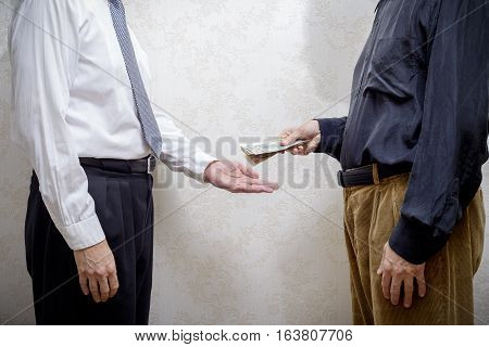 Corrupted man paying a Dollars banknotes bribe to a businessman or politician accepting corruption poster