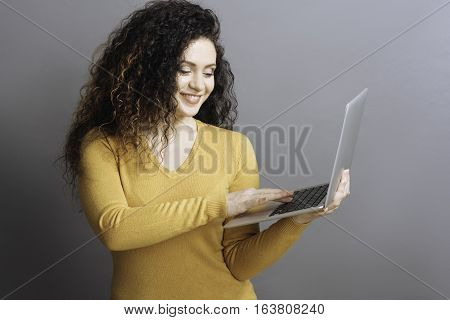 One moment. Positive delighted female wearing yellow jersey holding grey laptop in the left hand while working with it