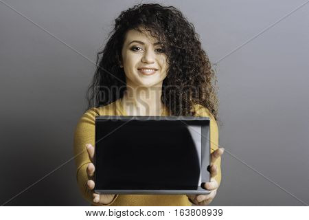 Buy it. Nice smiling brunette holding computer in both hands in front of herself looking at camera standing over grey background