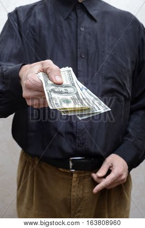 Businessman, Or Politician, Offering A Dollar Banknotes Bribe For Corruption