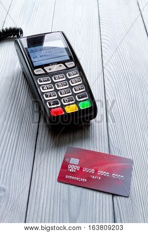payment card through terminal in store top view on wooden background