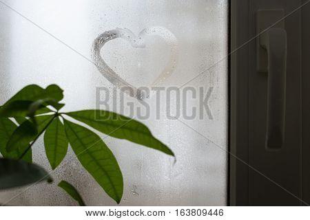 Inscription on the sweaty window glass shape of heart. Love and romance symbol