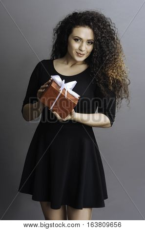 Time for surprise. Pretty woman with enigmatical smile looking straight at camera with pressed lips keeping present in both hands, isolated on grey