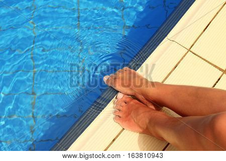 a female legs in the pool water