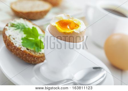 Traditional breakfast with perfect soft boiled egg sandwich with butter and dill coffee cup on a table. International cuisine food.