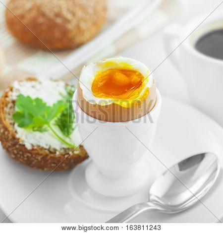 Perfect soft boiled egg open bread sandwich with butter and cup of coffee on a table. Traditional food for healthy breakfast.