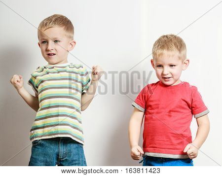 Free time fun and independence. Little boys play together indoors make silly gestures emotions. Blonde siblings wear colorful clothes.