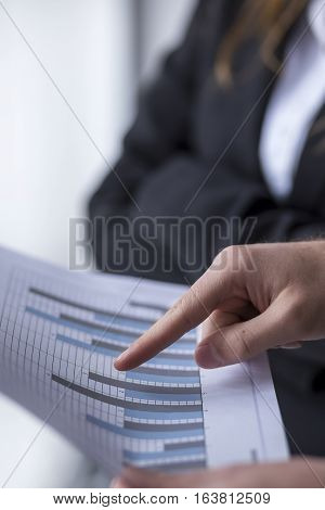 Detail of a two business colleagues analyzing data in an office, looking at some charts