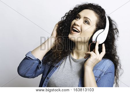 Sing with me. Emotional attractive girl while hearing sounds starting singing and looking upwards