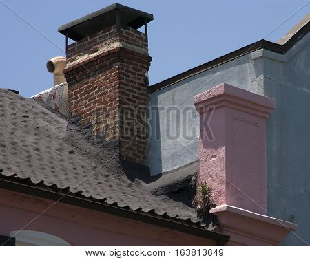 Different styles of old chimneys on the rooftops of historic buildings in downtown Charleston, South Carolina.