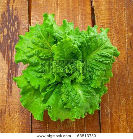 resh lettuce. Healthy vegetarian food on a old brown table. Abstract concept. Top view close-up.