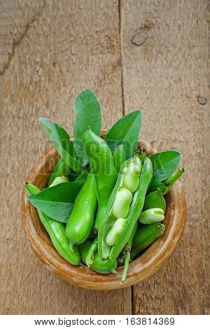 Bowl of podded green broad beans on a wooden table. Healthy organic food. Top view.