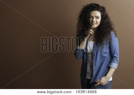Deep in thoughts. Positive delighted girl wearing jeans shirt holding left hand in pocket looking sideways isolated on brown background