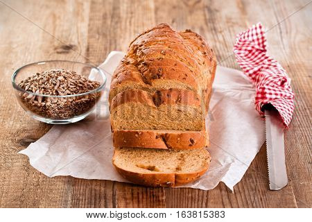 Whole wheat bread on baking paper with seeds.