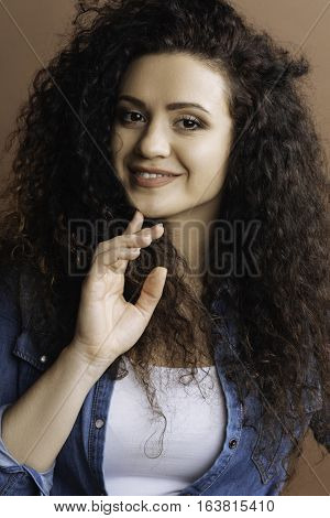 Tenderness mood. Young attractive smiling woman wearing jeans shirt keeping right hand on the chin standing over grey background