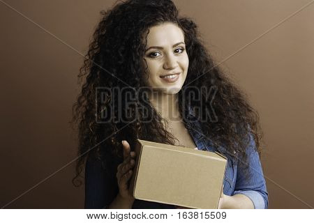 My parcel. Young woman with curly hair smiling holding parcel in her hands looking straight at camera, isolated on brown background