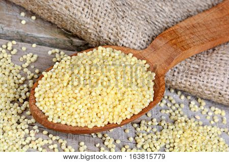Millet seeds on wooden table close up