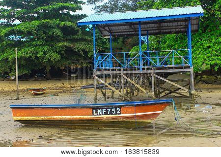 Labuan,Malaysia-Jan 3,2017:Fishing boat in Tanjung Aru jetty,Labuan island,Malaysia, fishing village with blue sky and clouds at low tide.