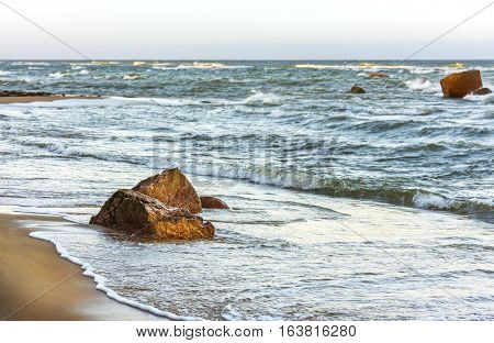 Stormy seascape of several rocks in a turbulent ocean sandy beach at foreground