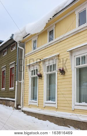 Heavy load of snow hang over an eaves of a yellow timber building at winter