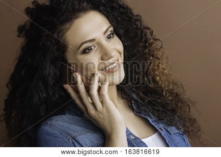 Pleased with speaking. Portrait of pretty woman with curly hair looking sideways using phone while speaking with friends