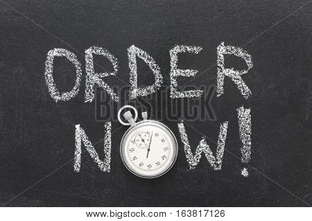 order now watch phrase handwritten on chalkboard with vintage precise stopwatch used instead of O
