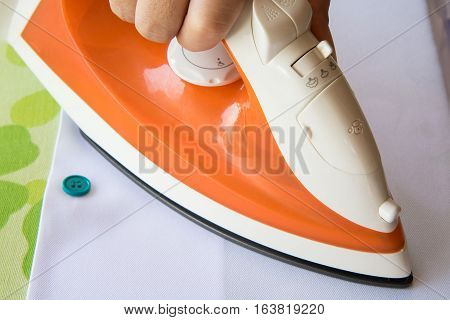 ironing the cloth with hot stream iron.