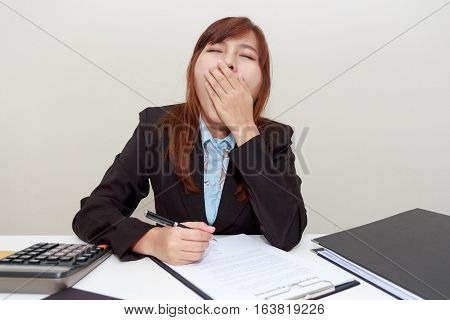 Businesswoman yawn or feel sleepy while working at office after having launch