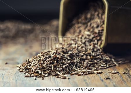 Cumin.Caraway seeds on wooden table. Cumin in vintage bronze bowl and spoon.