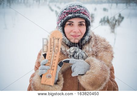 Young woman in the snow with a thermometer measuring the temperature outdoor
