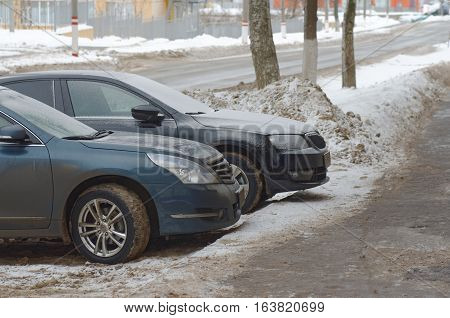 SARANSK, RUSSIA - JANUARY 1, 2017: Nissan Teana and Skoda Octavia parked at city street. Photo taken at cloudy day.