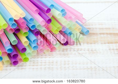 Multi colored plastic drinking straws, copy space