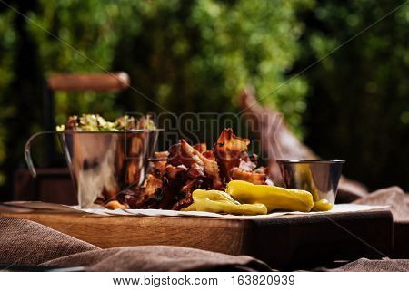 So many dishes. Close up of a wooden tray with salad and bacon standing in a restaurant outdoors.