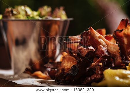 Well prepared. Close up of fried tasty bacon standing on a wooden tray while being cooked with salad in a restaurant