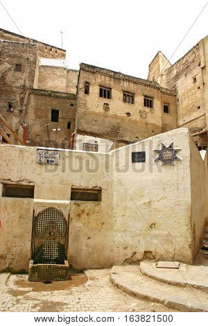 FEZ MOROCCO - MAY 19 2006: Water fountain houses and signs on a typical residential street in the ancient medina Fes el Bali in Fez Morocco.